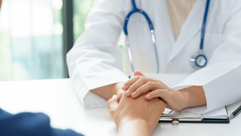Caring doctor holding patient's hand